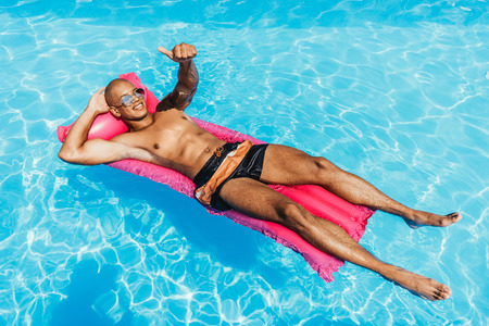 african american man showing thumb up while sunbathing on inflatable mattress in swimming pool Фото со стока