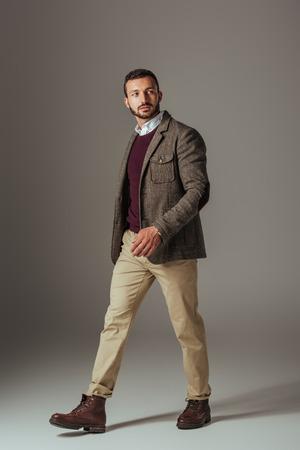 stylish man posing in beige pants and autumn tweed jacket, on grey Stock Photo