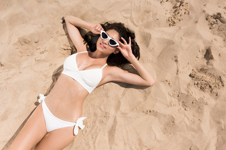 top view of sexy young woman in sunglasses and bikini sunbathing on sandy beach