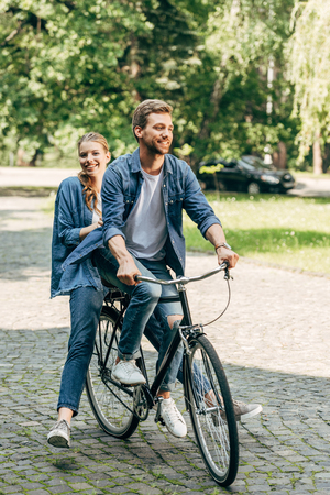 happy young couple riding bicycle together at park 版權商用圖片