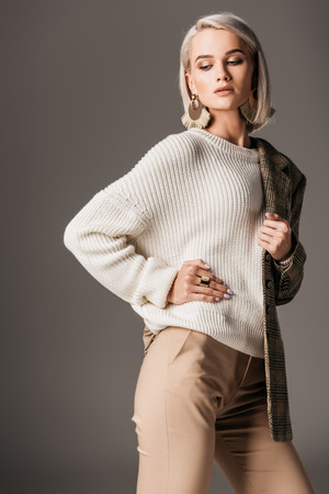 fashionable girl posing in white sweater and tweed jacket on one shoulder, on grey