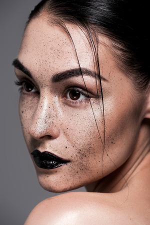 attractive model with black lips and freckles, isolated on grey 写真素材