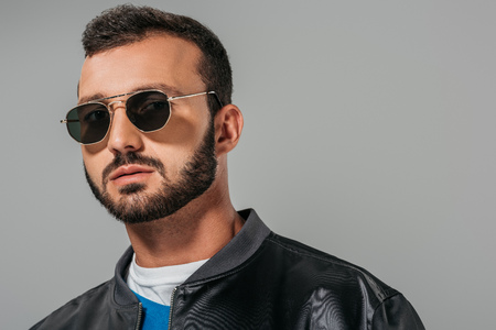 handsome man posing in stylish bomber and trendy sunglasses,  isolated on grey