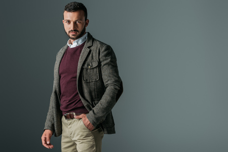 handsome bearded man posing in autumn tweed jacket, isolated on grey Stock Photo
