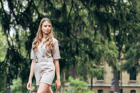 beautiful young woman in stylish overall walking by park