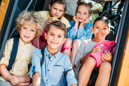 group of smiling schoolchildren sitting on stairs of school bus and looking at camera