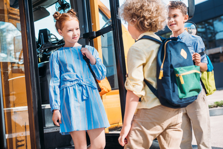 group of schoolchildren standing near school bus and talking Stock Photo