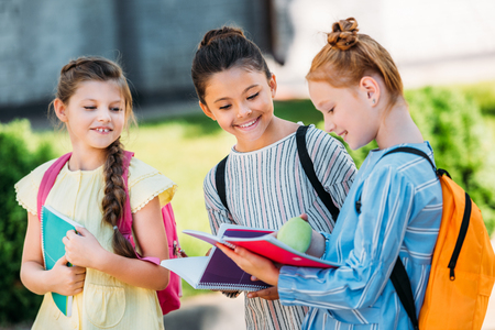 group of happy schoolgirls with notebooks walking together after school Stock Photo