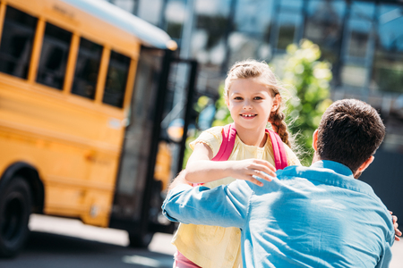 back view of father and daughter embracing in front of school bus Stock Photo