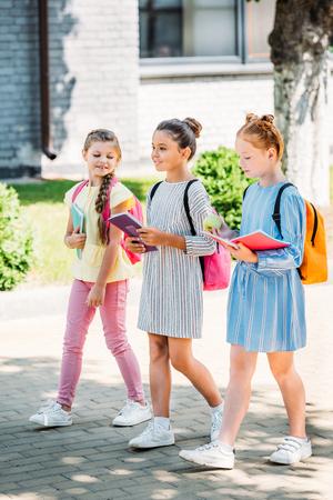 groep mooie schoolmeisjes met notitieboekjes die samen na school lopen Stockfoto