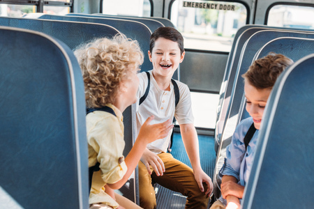 group of adorable schoolboys having fun together while riding on school bus Stok Fotoğraf