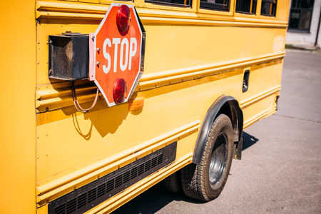 partial view of school bus with stop sign
