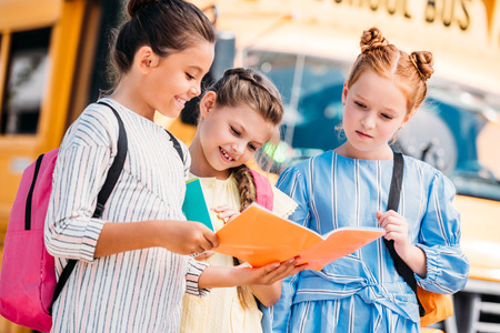 group of little schoolgirls looking at notebook in front of school bus Imagens