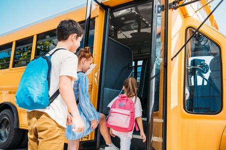 rear view of pupils with backpacks entering school bus Foto de archivo