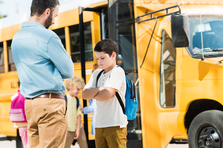 father preaching his son in front of school bus