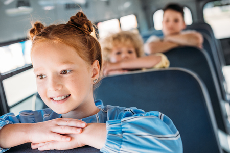 close-up portrait of happy little schoolgirl riding on school bus with classmates behind Banco de Imagens