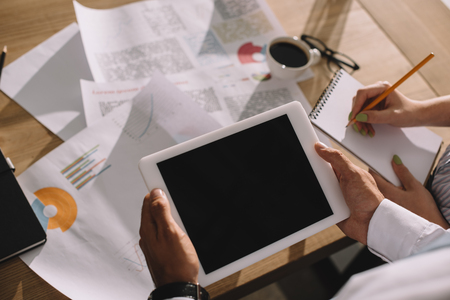 businesspeople using digital tablet and doing paperwork in office