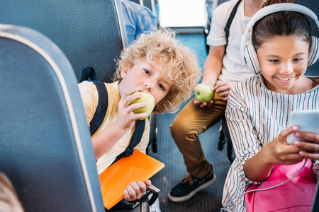 adorable little schoolboy eating apple while riding on school bus with classmates