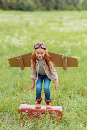 smiling kid in pilot costume jumping from retro suitcase in summer field Stock Photo