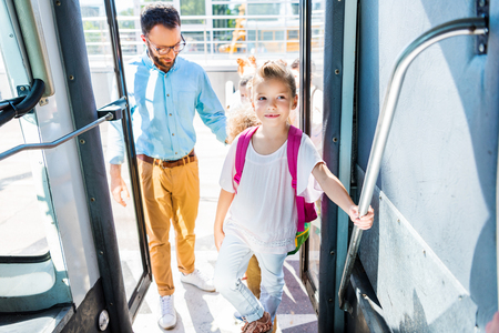 schoolgirl entering school bus with teacher while going on excursion