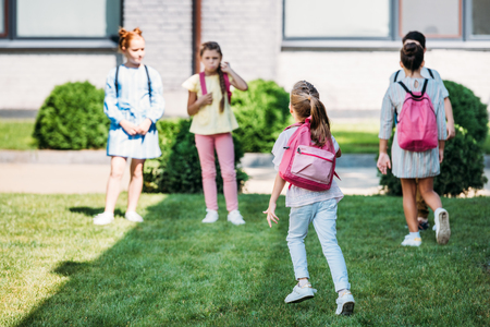 rear view of pupils with bakpacks waling by school garden 스톡 콘텐츠