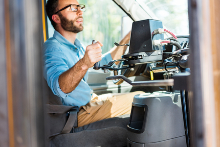 handsome school bus driver losing door with lever and looking at rear mirror Stockfoto - 108126258