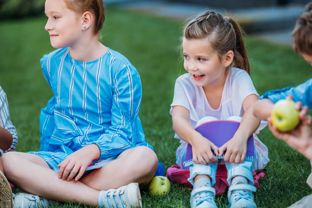 adorable little schoolgirls sitting on grass and laughing together