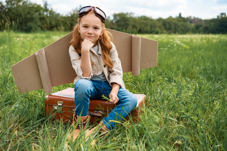 adorable kid in pilot costume sitting on retro suitcase in summer field