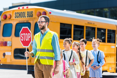 traffic guard crossing road with schoolchildren in front of school bus Foto de archivo