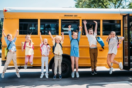 group of happy pupils jumping in front of school bus and looking at camera