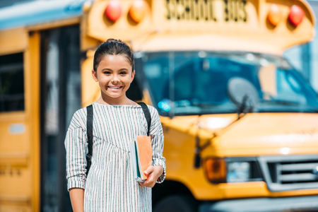 adorable little schoolgirl with notebooks looking at camera in front of school bus