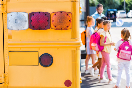 rear lights of school bus with pupils blurred on background Stock Photo