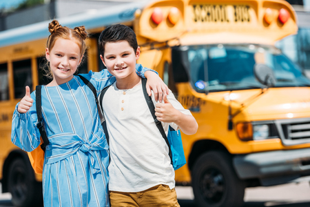 happy little scholars showing thumbs up and looking at camera in front of school bus