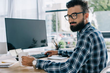 young successful seo sitting at workplace with blank computer screen and looking at camera Stock fotó - 108130514