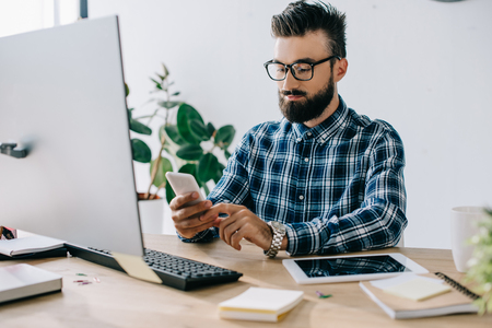handsome bearded young businessman using smartphone at workplace Stock fotó - 108130527