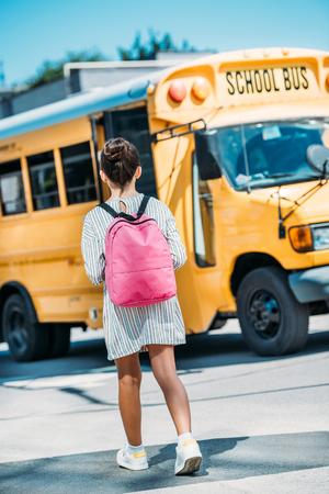 rear view of schoolgirl with backpack standing in front of school bus