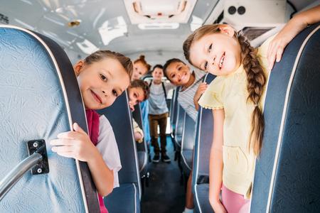 Gruppe von niedlichen Schulkindern, die auf Schulbus reiten und Kamera betrachten