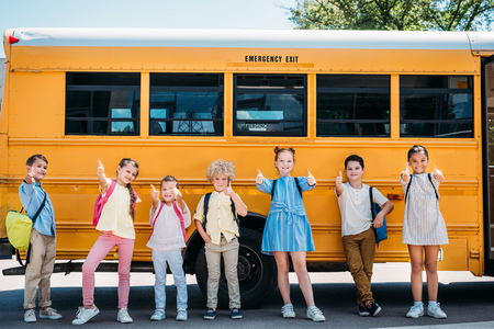 group of adorable schoolchildren standing in front of school bus and showing thumbs up