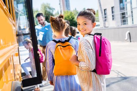 Klein schoolmeisje schoolbus invoeren met klasgenoten terwijl leraar in de buurt van deur Stockfoto - 108148387
