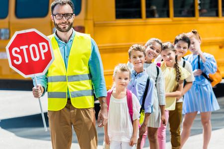 Guardia de tráfico miling con eruditos mirando a la cámara delante del autobús escolar
