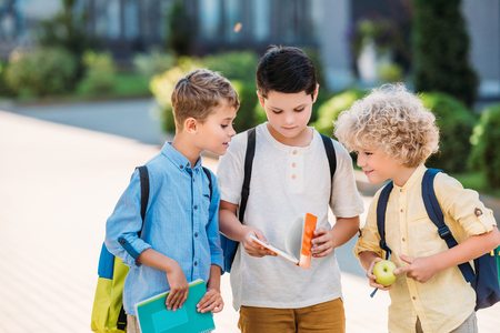 group of adorable schoolboys looking at notebook together