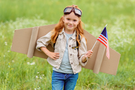 portrait of smiling kid in pilot costume with american flagpole standing in meadow