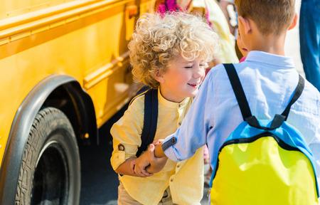 rear view of adorable scholars playing near school bus Reklamní fotografie