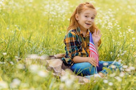 emotional kid with american flagpole resting on green grass in field Stockfoto