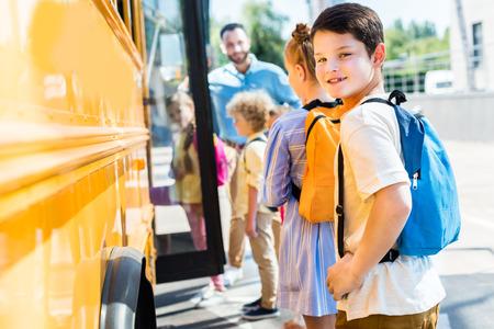 little schoolboy entering school bus with classmates while teacher standing near door