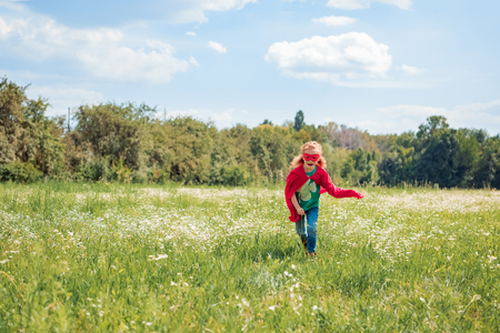 little kid in red superhero costume running in meadow on summer day 写真素材