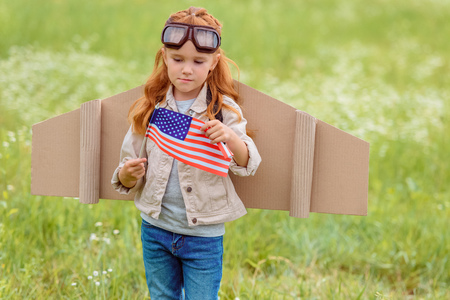 portrait of kid in pilot costume with american flagpole standing in meadow