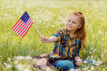 cute kid with american flagpole resting on green grass in field