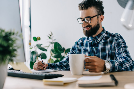 successful smiling seo with cup of coffee and computer writing notes at workplace Stock fotó - 108154899