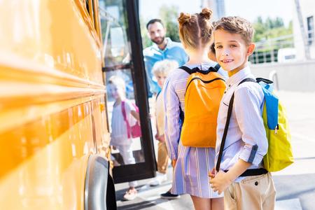 adorable schoolboy entering school bus with classmates while teacher standing near door